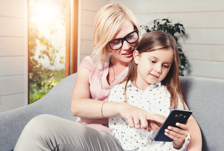 Pretty blonde mother in glasses and little cute brunette daughter sitting on the sofa and watching photos on the mobile phone