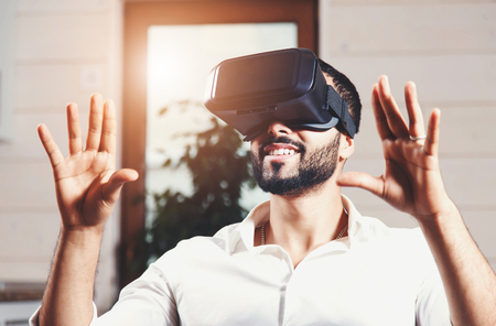 Multicultural bearded man wearing virtual reality goggles and watching video in the modern flat Foto de archivo