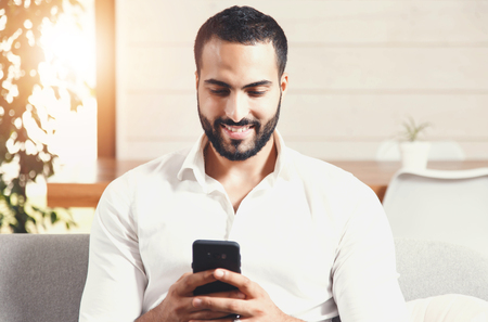 Sexy bearded man in white shirt sitting on the sofa and writting message on the smartphone, using app concept