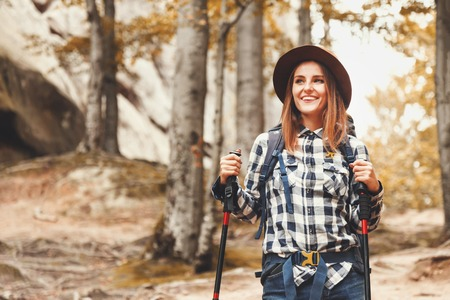 Happy beautiful young woman wearing brown hat walking with trecking poles and looking on the forest views, she thinking about her trip and dreaming about new places that she visit