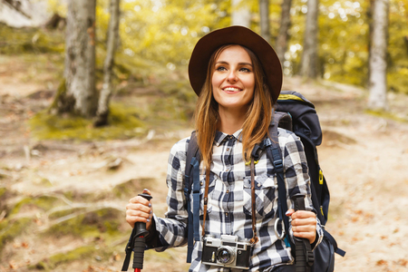 Happy young woman with backpack wearing brown hat, plaid shirt, jeans and brown boots walking with trecking poles, smiling and looking on the wonderful rocks, travelling concept