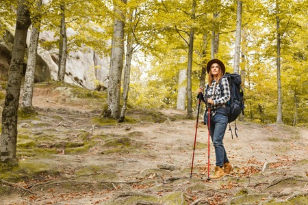 Serious young woman with backpack wearing brown hat, plaid shirt, jeans and brown boots walking with trecking poles and looking on the forest views, she thinking about her route and trip, travelling concept