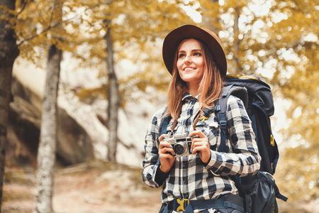 Happy young woman with backpack wearing brown hat, plaid shirt, jeans and brown boots walking with trecking poles, looking on the wonderful rocks and getting ready to taking a photo, travelling concept