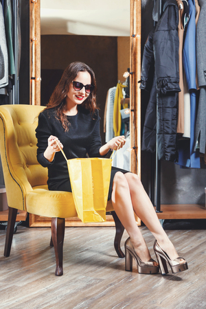 Fashion young brunette hair girl wearing sunglasses sitting on the yellow armchair with yellow shopping bag in the shopping center, black friday concept