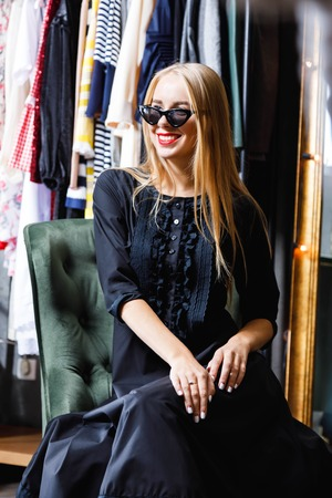 Fashion blonde happy girl in black dress wearing sunglasses sitting on the green armchair and smiling in the shopping center, black friday concept Stock Photo