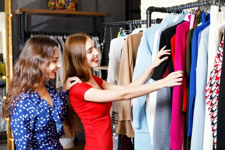 Two pretty cheerful young girls choosing clothes in fashion mall, concept of consumerism, Black Friday, sale, rich life