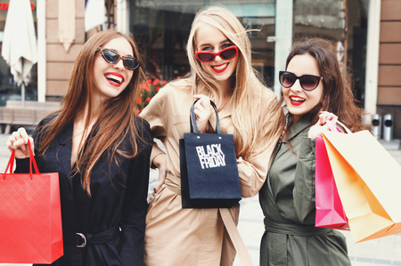 Gorgeous girls wearing trench-coat and sunglasses posing with colorful shopping bags at shopping mall background during shopping process, concept of consumerism, sale, rich life Stock Photo