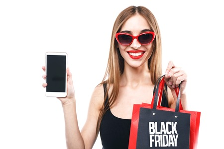 Sexy brunette woman wearing black dress and sunglasses holding black friday shopping bag and showing smartphone on the white background, concept of consumerism, sale, rich life