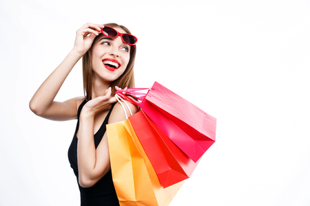 Sexy brunette woman wearing black dress and sunglasses standing with colorful shopping bags and looking up on the white background, concept of consumerism, sale, rich life