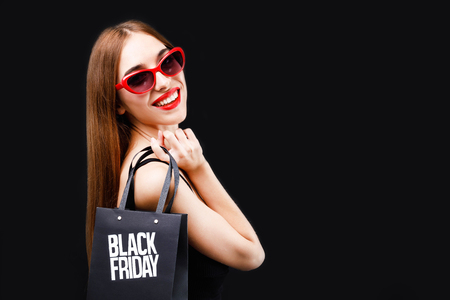 Elegant rich brunette woman wearing black dress and sunglasses smiling with black friday shopping bag on the black background, black friday concept Stock Photo