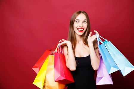 Side view of young attractive woman with bright lipstick in black dress showing paper shopping bags and looking up on red background, black friday concept