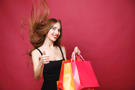 Young sexy smiling woman wearing black dress posing in flicked her long hair, showing thumb up and holding colorful shopping bags on the red background, black friday concept Stock Photo