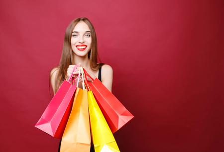 Side view of young attractive smiling woman with bright lipstick in black dress standing in studio with paper shopping bags and looking at camera on red background, black friday concept
