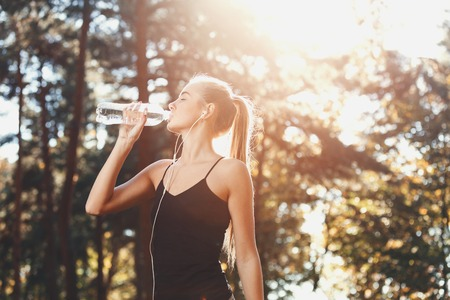Portrait of young athletic long haired woman wearing sporty clothes listening music and drinking water in the sunny park