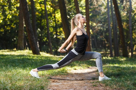Sporty long-haired young woman wearing black shirt stretching before the jogging in the sunny park and enjoying of the good weather Stock Photo