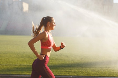 Positive athletic attractive blonde long haired woman in sportswear standing listening music while jogging at the football stadium, green grass background