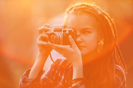 Hipster amazing photograph girl with dreads making pictures of the nature in the sunset in the forest, outdoor view