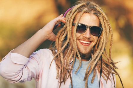 Portrait of hipster blonde bearded boy with dreads wearing headphones and glasses walking, smiling and listening his favorite music outdoors an the sunny autumn day Stock Photo