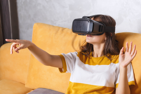 Attractive long-haired girl in pullover gesturing while testing VR device, she sitting on the yellow sofa in the light living room, future technology concept Stock Photo