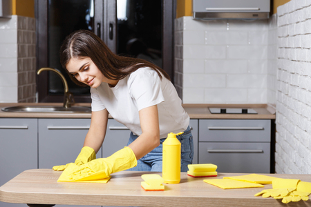 Pretty long-haired girl in white t-shirt wearing yellow rubber gloves cleaning the table on the kitchen Banque d'images