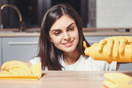 Cute long-haired brunette girl in white t-shirt wearing yellow rubber gloves pours liquid on the table on the kitchen