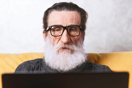 Concentrated senior bearded man in glasses and grey pullover working with laptop while sitting on the yellow sofa in the light living room, modern technology, communication concept Stock fotó