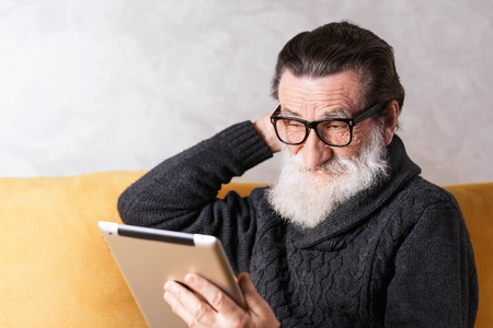 Senior bearded man in glasses wearing grey pullover sitting on a yellow sofa in his light living room and looking doubtfully on the digital tablet