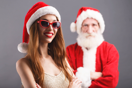 Young mrs. Claus wearing Santa hat and sunglasses standing and smiling, Santa Claus standing behind on the gray background, New Year, Christmas, holidays, souvenirs, gifts, shopping, discounts, shops, Snow Maiden Santa Claus,make-up, hairstyle, carnival.