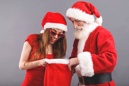 Santa Claus with white beard wearing sungasses and young mrs. Claus wearing Santa hat, red dress and sunglasses standing on the gray background, surprised mrs. Santa searching some presents in the Santa Claus bag, New Year, Christmas, holidays, souvenirs, gifts, shopping, discounts, shops, Snow Maiden Santa Claus,make-up, hairstyle, carnival.