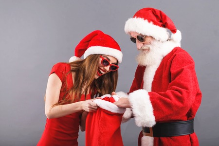 Santa Claus with white beard wearing sungasses and young mrs. Claus wearing Santa hat, red dress and sunglasses standing on the gray background, mrs. Santa searching some presents in the Santa Claus bag, New Year, Christmas, holidays, souvenirs, gifts, shopping, discounts, shops, Snow Maiden Santa Claus,make-up, hairstyle, carnival.