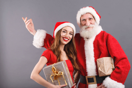 Santa Claus with white beard wearing sungasses and young mrs. Claus wearing Santa hat, red dress and sunglasses standing on the gray background and congratulates with Merry Christmass and Happy New Year, New Year, Christmas, holidays, souvenirs, gifts, shopping, discounts, shops, Snow Maiden Santa Claus,make-up, hairstyle, carnival.