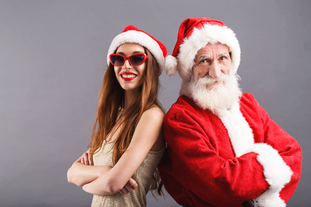 Santa Claus and young mrs. Claus wearing Santa hat and sunglasses standing and smiling on the gray background, New Year, Christmas, holidays, souvenirs, gifts, shopping, discounts, shops, Snow Maiden Santa Claus,make-up, hairstyle, carnival.