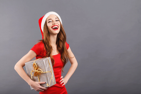 Beautiful christmas woman wearing Santa hat and red dress laughing and holding a present, New Year, Christmas, holidays, souvenirs, gifts, shopping, discounts, shops, Snow Maiden Santa Claus,make-up, hairstyle, carnival.