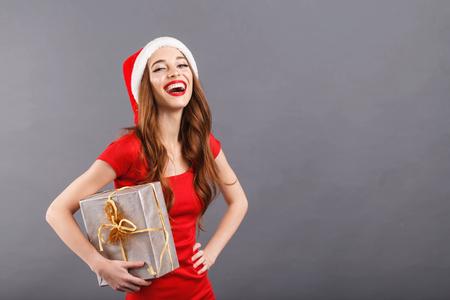 Schöne Weihnachtsfrau mit Weihnachtsmütze und rotem Kleid, die ein Geschenk lacht und hält, Neujahr, Weihnachten, Feiertage, Souvenirs, Geschenke, Einkaufen, Rabatte, Geschäfte, Schneewittchen-Weihnachtsmann, Make-up, Frisur, Karneval.