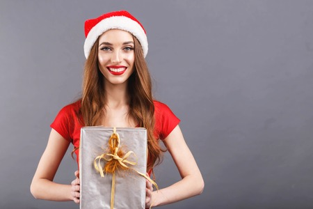 Beautiful christmas woman wearing Santa hat and red dress looking at camera and giving a gift, New Year, Christmas, holidays, souvenirs, gifts, shopping, discounts, shops, Snow Maiden Santa Claus,make-up, hairstyle, carnival.