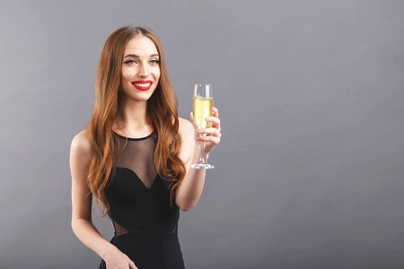 Pretty long haired woman with red lips wearing black dress standing on the gray background while says a toast and drinking champagne, New Year, Christmas, holidays, souvenirs, gifts, shopping, discounts, shops, make-up, hairstyle, carnival. Banco de Imagens