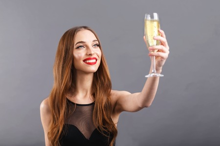 Pretty long haired woman with red lips wearing black dress says a toast and drinking champagne, New Year, Christmas Banco de Imagens