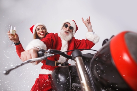 Santa Claus with white beard wearing sungasses and young mrs. Claus wearing Santa hat, red sweater and sunglasses Mrs. Claus holding champagne and Santa Claus showing a rock gesture, while riding a motorcycle when snowing, New Year, Christmas, holidays, souvenirs, gifts, shopping, discounts, shops, Snow Maiden Santa Claus,make-up, hairstyle, carnival.