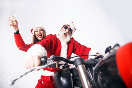 Santa Claus with white beard wearing sungasses and young mrs. Claus wearing Santa hat, red sweater and sunglasses riding a motorcycle when snowing, Mrs. Claus drinking champagne, New Year, Christmas, holidays, souvenirs, gifts, shopping, discounts, shops, Snow Maiden Santa Claus,make-up, hairstyle, carnival. Stock Photo