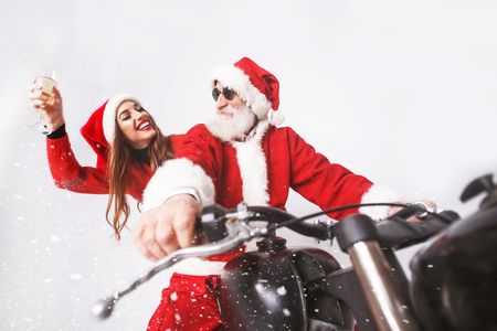 Santa Claus with white beard wearing sungasses and young mrs. Claus wearing Santa hat, red sweater and sunglasses riding a motorcycle when snowing, Mrs. Claus laughing with champagne, New Year, Christmas, holidays, souvenirs, gifts, shopping, discounts, shops, Snow Maiden Santa Claus,make-up, hairstyle, carnival.