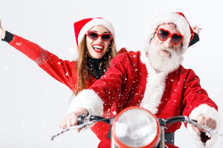 Santa Claus with white beard wearing sungasses and young mrs. Claus wearing Santa hat, red sweater and sunglasses riding a motorcycle, New Year, Christmas, holidays, souvenirs, gifts, shopping, discounts, shops, Snow Maiden Santa Claus,make-up, hairstyle, carnival. Stock Photo