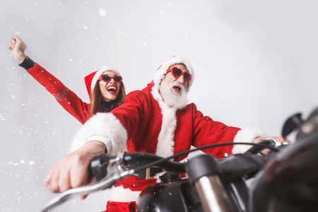 Santa Claus with white beard wearing sungasses and young mrs. Claus wearing Santa hat, red sweater and sunglasses rejoicing in the snow while riding a motorcycle when snowing, New Year, Christmas, holidays, souvenirs, gifts, shopping, discounts, shops, Snow Maiden Santa Claus,make-up, hairstyle, carnival. Stock Photo
