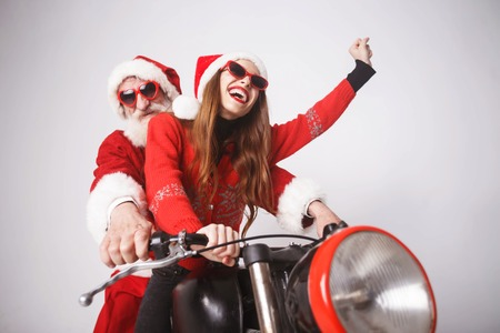 Happy young mrs. Claus wearing Santa hat, red sweater and sunglasses riding with Santa Claus on a motorcycle on the high speed, New Year, Christmas, holidays, souvenirs, gifts, shopping, discounts, shops, Snow Maiden Santa Claus,make-up, hairstyle, carnival. Stock Photo