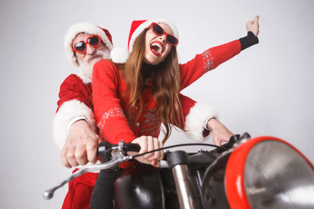 Happy young mrs. Claus wearing Santa hat, red sweater and sunglasses rejoicing while riding with Santa Claus on a motorcycle on the high speed New Year, Christmas, holidays, souvenirs, gifts, shopping, discounts, shops, Snow Maiden Santa Claus,make-up, hairstyle, carnival. Stock Photo