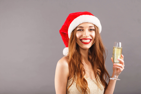 Delightful long haired woman in red santa claus hat with red lips standing on the gray background and holding a glass of champagne, New Year, Christmas, holidays, souvenirs, gifts, shopping, discounts, shops, Snow Maiden Santa Claus,make-up, hairstyle, carnival.