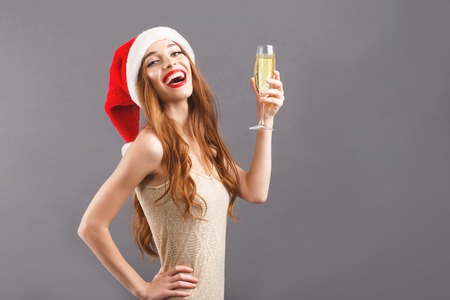 Delightful long haired woman in red santa claus hat with red lips standing on the gray background, she says a toast and drinking champagne, New Year, Christmas, holidays, souvenirs, gifts, shopping, discounts, shops, Snow Maiden Santa Claus,make-up, hairstyle, carnival.