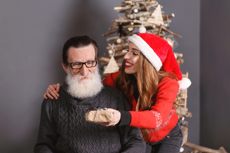 Handsome bearded senior dad wearing glasses and gray sweater accepts a gift from his young long haired daughter in the red sweater wearing Santa hat, he feeling shocked and surprised, New Year, Christmas, holidays, souvenirs, gifts, shopping, discounts, shops, Snow Maiden Santa Claus,make-up, hairstyle, carnival.