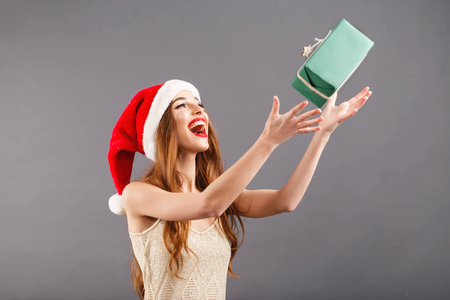 Fancy long haired woman in red santa claus hat with red lips standing on the gray background and tossing a present box, New Year, Christmas, holidays, souvenirs, gifts, shopping, discounts, shops, Snow Maiden Santa Claus,make-up, hairstyle, carnival.