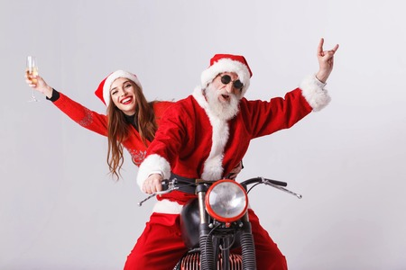 Santa Claus with white beard wearing sungasses and young mrs. Claus wearing Santa hat, red sweater and sunglasses riding a motorcycle, Mrs. Claus holding champagne and Santa Claus showing a rock gesture, New Year, Christmas, holidays, souvenirs, gifts, shopping, discounts, shops, Snow Maiden Santa Claus,make-up, hairstyle, carnival.