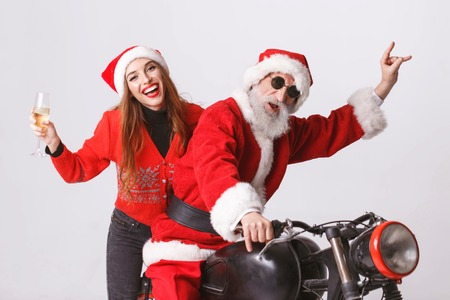 Santa Claus with white beard wearing sungasses and young mrs. Claus wearing Santa hat, red sweater and sunglasses Mrs. Claus holding champagne and Santa Claus showing a rock gesture, while riding a motorcycle, New Year, Christmas, holidays, souvenirs, gifts, shopping, discounts, shops, Snow Maiden Santa Claus,make-up, hairstyle, carnival.